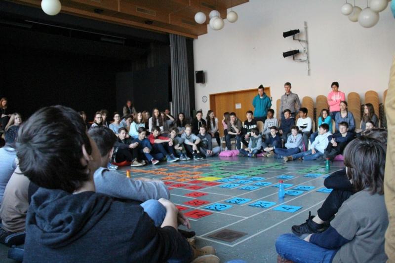 Spielerischer Start: Jeweils vier Schulklassen treffen sich in der Aula zum Leiterlispiel. (Bild: Manuel Scherrer / zvg)