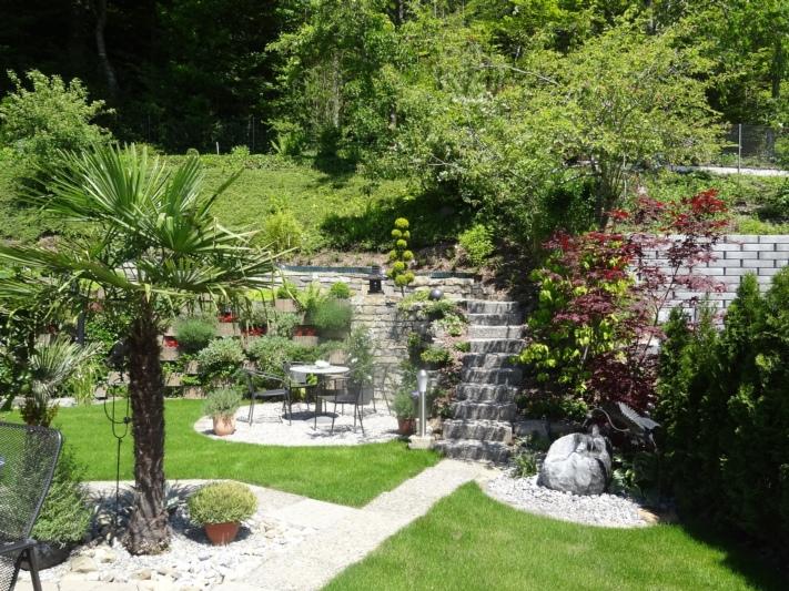Neu gestalteter Garten mit Sitzplatz, Natursteinmauer und neuer Bepflanzung.