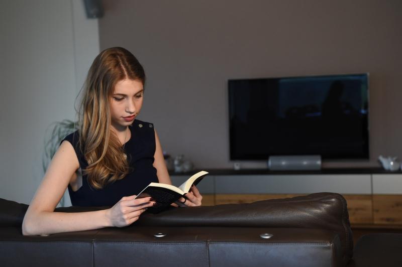 Die Miss BERN-OST liest gerne - hier auf dem Sofa im Wohnzimmer.