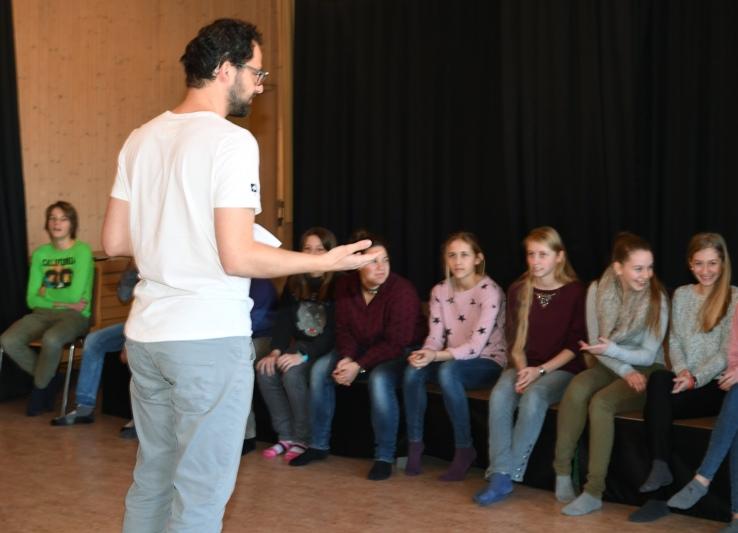 Lehrer Sascha Wüthrich erklärt den Schülerinnen und Schülern die nächste Szene des Theaterstücks. (Bild: Res Reinhard)