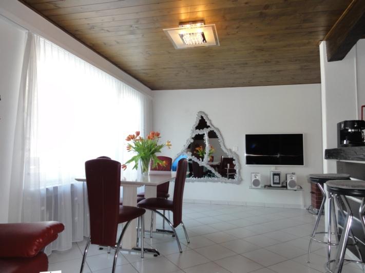 Wohnzimmer mit Esstisch, rechts Bartheke