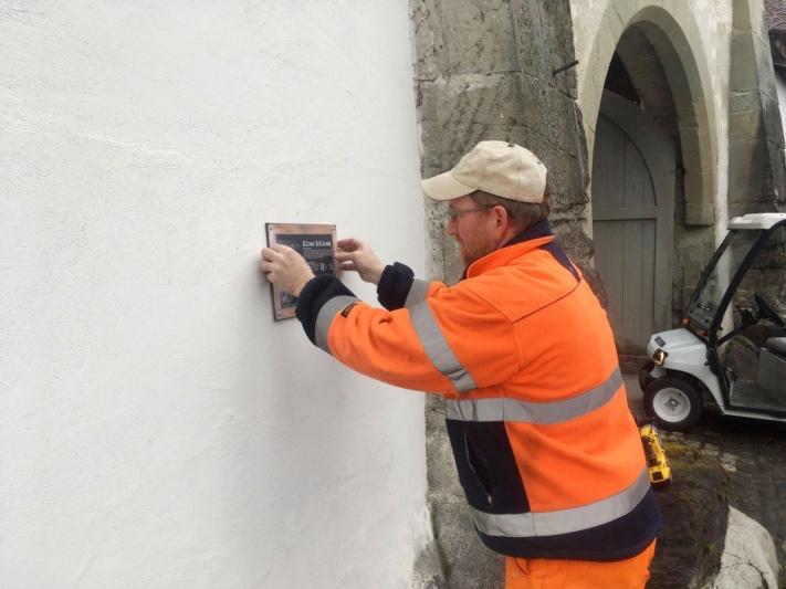 Ein Mitarbeiter der Gemeinde montiert das Panel für das Alte Schloss. (Bilder: Sigmund von Wattenwyl)