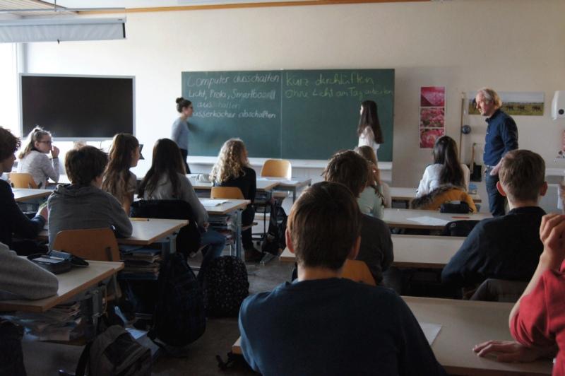 Ohne digitale Wandtafel und elektrisches Licht: Die Schülerinnen und Schüler der Klasse 9A bestimmen am Black Out Day gemeinsam mit Lehrer Urs Plüss ihr Klimaziel. (Bild: Eva Tschannen)